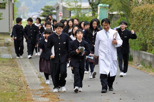 森に向かって歩く先生と生徒たち